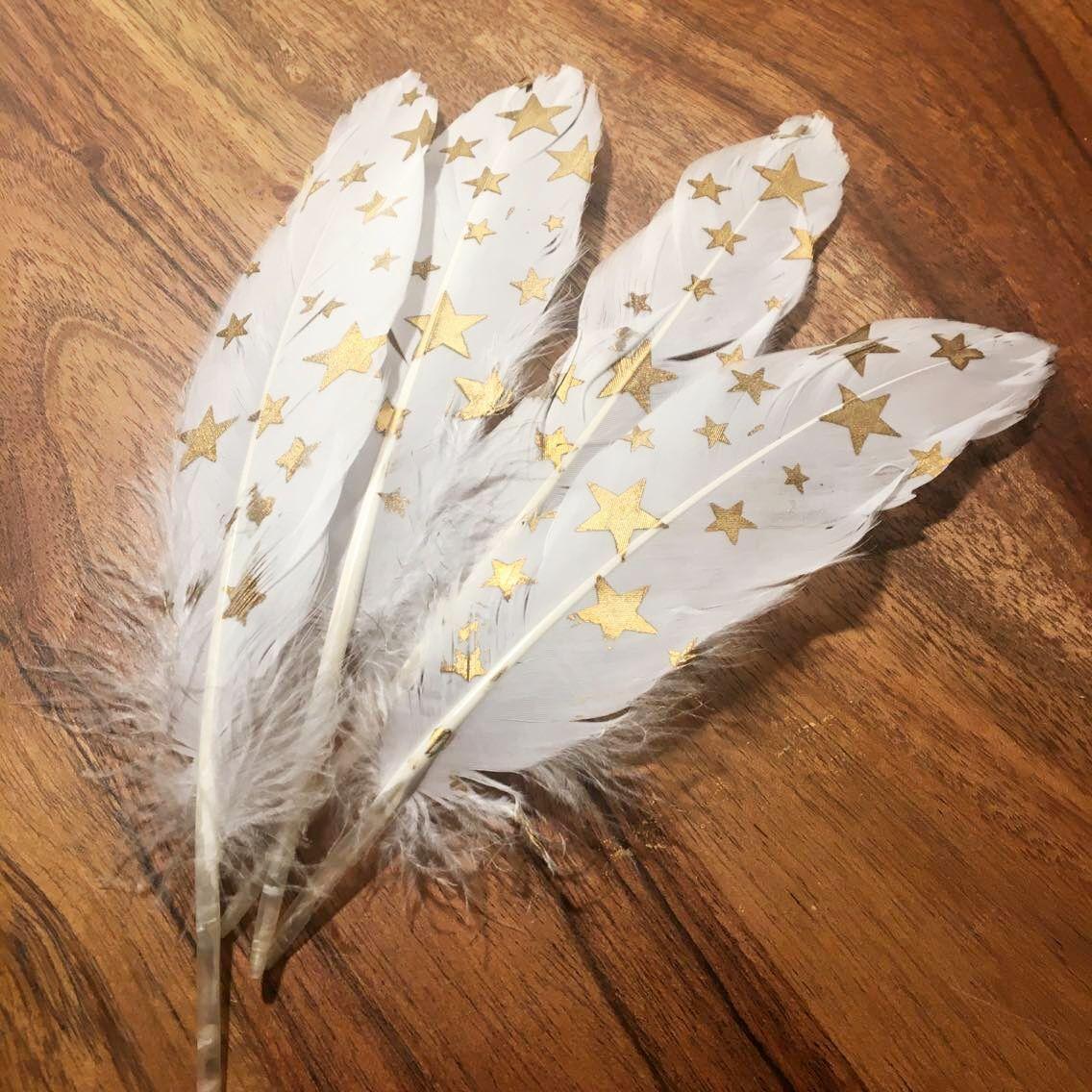 Peří bílé, dlouhé, zlaté hvězdy